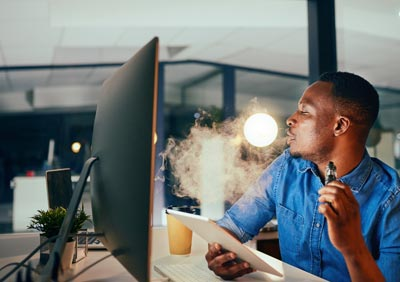 Man-at-work-vaping-e-cigarette-at-his-desk