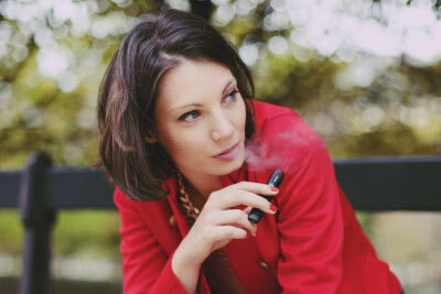 Woman Vaping on a Bench